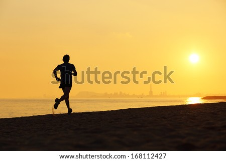 Jogger silhouette running on the beach at sunset with the horizon in the background - stock photo
