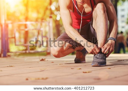 Jogger tying shoe laces before jogging - stock photo