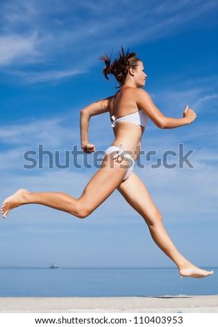 Jogging. Girl running along the beach - stock photo