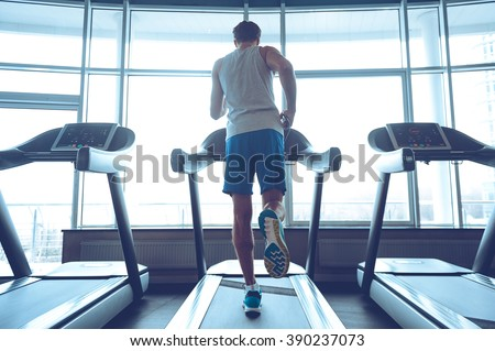 Jogging his way to good health. Full-length rear view of young man in sportswear running on treadmill in front of window at gym - stock photo