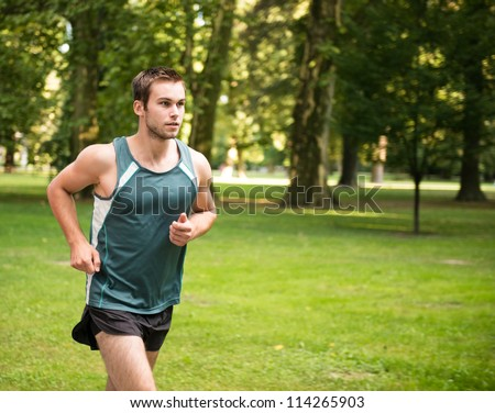 Jogging lifestyle - young attractive man running in park - stock photo