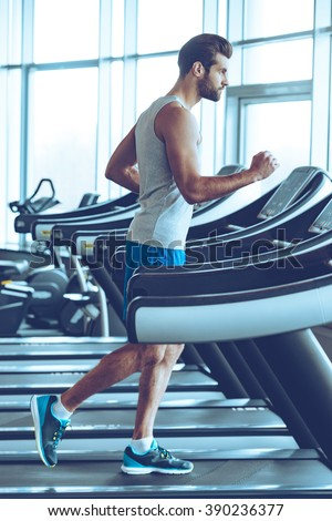 Jogging on treadmill. Side view full length of young man in sportswear running on treadmill at gym - stock photo