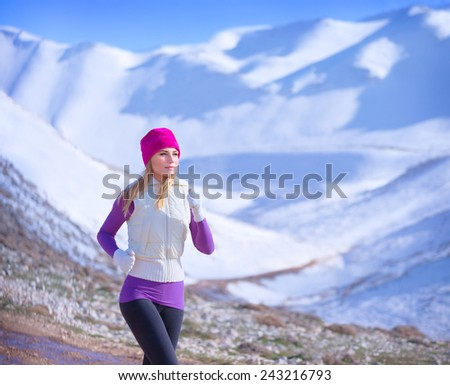 Jogging outdoors, cute sportive woman running along mountains covered with snow, workout in winter time, active lifestyle concept  - stock photo