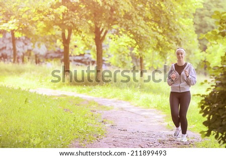 Jogging Sport Concept: Young Running Fitness Woman Training Outdoor in the Forest While LIstening to Music. Horizontal Image - stock photo