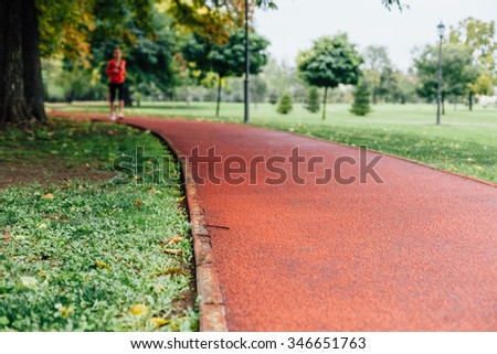 Jogging track in the park. Sportwoman blurred in background. - stock photo