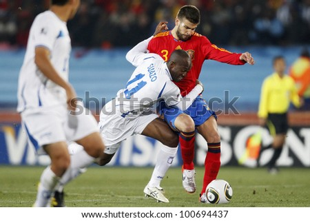 JOHANNESBURG, SOUTH AFRICA - JUNE 21:  David Suazo of Honduras (l) and Gerard Pique of Spain (r) fight for the ball during a 2010 World Cup match.  Editorial only.  No push to mobile device use. - stock photo