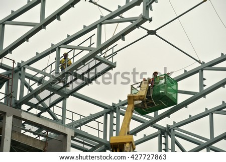 JOHOR, MALAYSIA -APRIL 12, 2016: Construction workers standing in the mobile crane bucket while working at high level in the construction site in Malaysia.    - stock photo