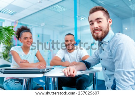 Join our creative team. Low angle portrait of beautiful young people sitting at the table and smiling at camera in creative space  - stock photo