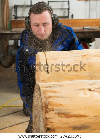 Joiner behind sawdust. He is cutting a tree trunk with chainsaw.  - stock photo