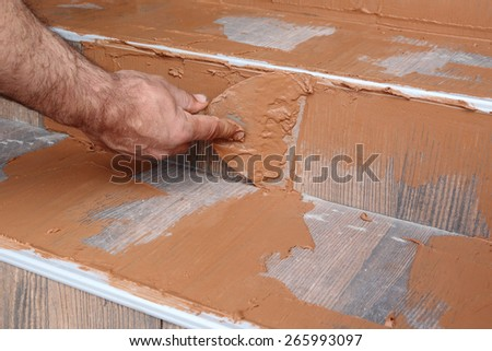 Joint sealing tiles, worker hand and trowel tool - stock photo