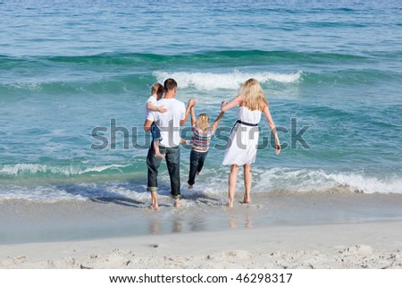 Jolly family walking on the sand at the beach - stock photo