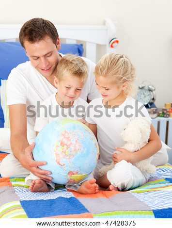 Jolly father and his children holding a terrestrial globe sitting on a bed - stock photo