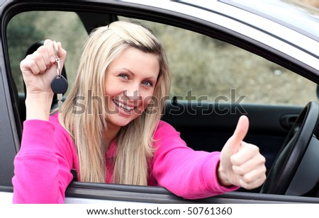 Jolly female driver showing a key with a thumb up after buying a new car - stock photo