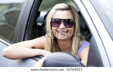 Jolly female driver wearing sunglasses sitting in her car smiling at the camera - stock photo