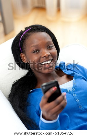 Jolly woman sending a text lying on a sofa in the living-room - stock photo