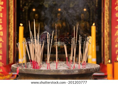 Joss Stick And Yellow Candle Burning At China Temple - stock photo