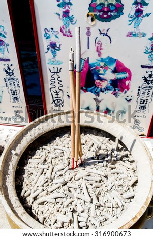 joss stick in joss stick pot on white background; incense in incense burner - stock photo