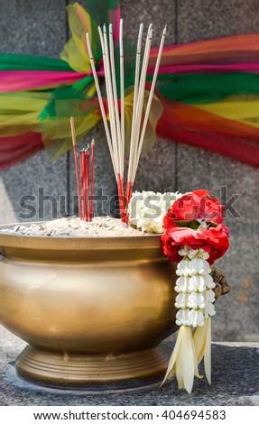 Joss sticks and Thai flower garland in incense burner on the altar(shrine) for worship Buddha  - stock photo