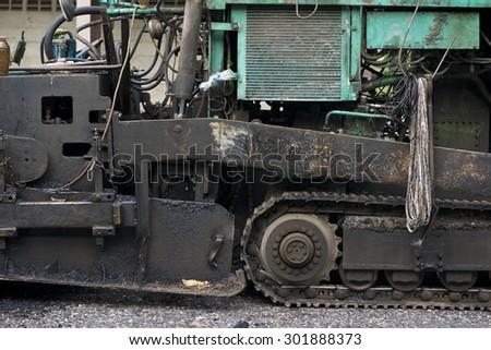 Jot asphalt gush out of asphalt paver machine - stock photo