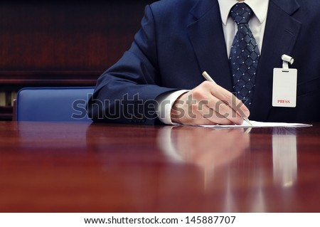 Journalist is doing paperwork at the conference, press concept, business concept. - stock photo