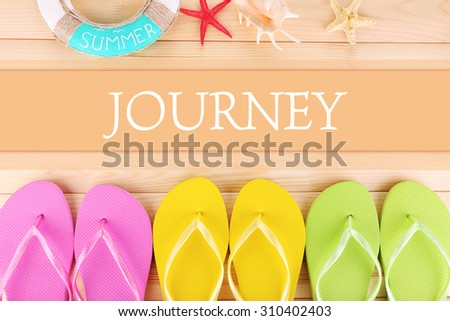 Journey concept. Bright flip-flops on wooden background - stock photo