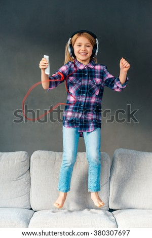 Joy and happiness. Beautiful little in headphones holding her smart phone and looking at camera with smile while jumping on the couch at home - stock photo