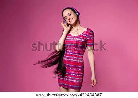 Joy and music. Colorful studio portrait of happy young brunette with the long hair woman with earphones is dancing and singing. - stock photo