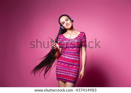 Joy and music. Colorful studio portrait of happy young brunette with the long hair woman with earphones - stock photo