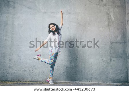Joy and music. Happy young brunette woman with earphones is dancing outdoors. - stock photo
