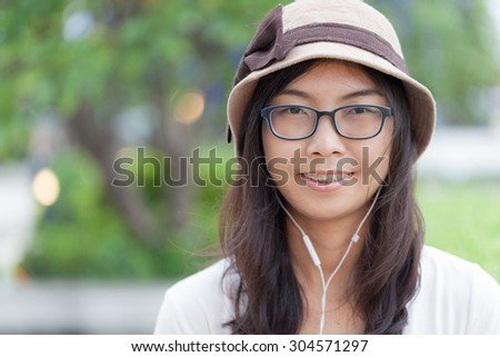 joy and relax asia woman listen music.wear hat and eyeglasses. - stock photo