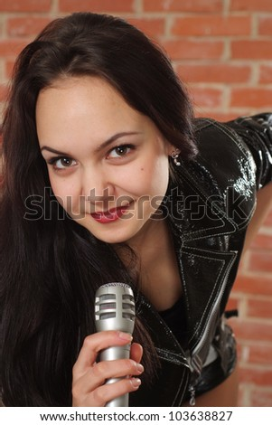 Joy Caucasian female with a microphone singing against a brick wall - stock photo
