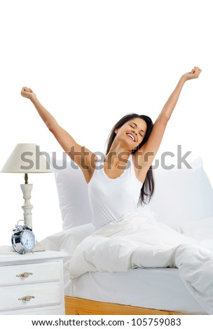 Joy cheerful happy woman waking up with a smile in bed and stretching her arms up - stock photo