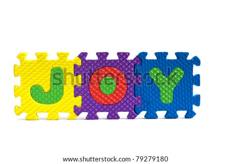 """Joy concept - the word """"Joy"""" written with alphabet puzzle letters isolated on white background - stock photo"""