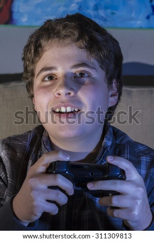 Joy. Teenage lifestyle. boy with joystick playing computer game at home. - stock photo