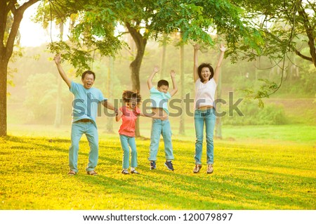 Joyful Asian family jumping together in the park - stock photo