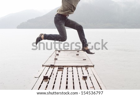 Joyful asian japanese young man jumping on a wooden pier while visiting a dreamy lake landscape with mountains during a cloudy and rainy day, outdoors. - stock photo