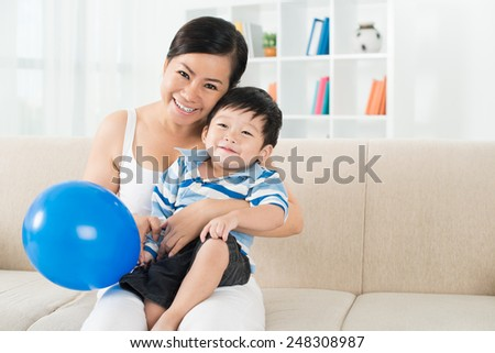 Joyful Asian mother and son sitting on the sofa at home - stock photo
