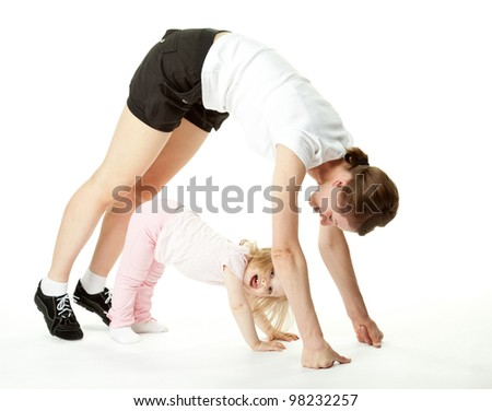 Joyful baby girl and her mother exercising; happy mother and daughter doing sport exercises together on white background - stock photo