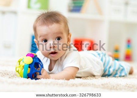 Joyful baby kid lying on the carpet with toy in nursery room - stock photo