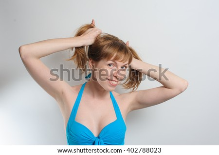 Joyful beautiful redhead young woman with freckles without makeup playing with her long hair, smiling happily at camera. Young woman wearing blue swimsuit. White background. - stock photo