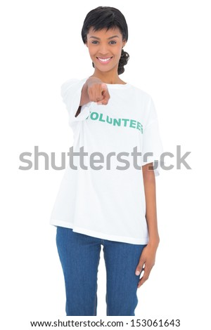 Joyful black haired volunteer pointing the camera with her finger on white background - stock photo