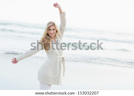 Joyful blonde woman in wool cardigan stretching her arms on the beach - stock photo