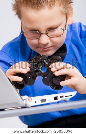 Joyful boy looking at computer screen in binoculars - stock photo