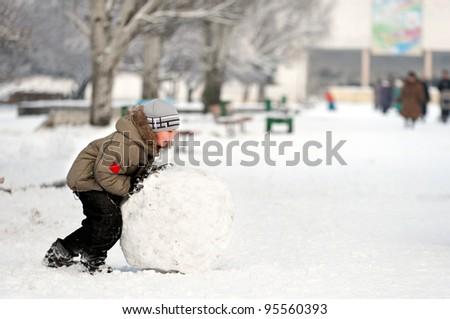 Joyful boy sculpts a snowman in park. Boy sculpts snowman. - stock photo
