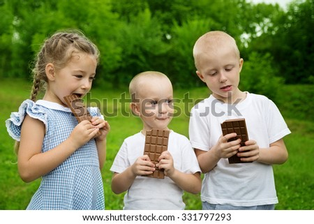 Joyful brothers and sister and chocolate bars. - stock photo