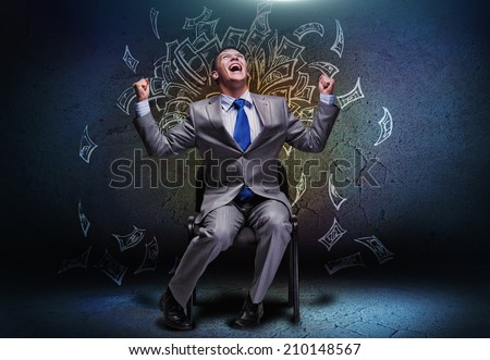 Joyful businessman sitting on chair under money rain - stock photo