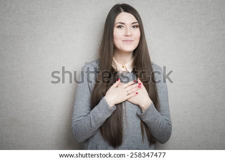 Joyful businesswoman holding hands on his chest - stock photo