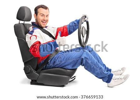 Joyful car racer sitting in a car seat and giving a thumb up isolated on white background - stock photo