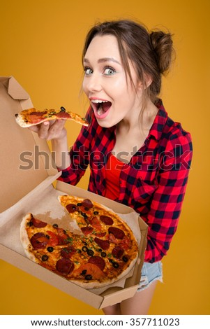 Joyful charming young woman in checkered shirt standing and tasting pizza over yellow background - stock photo