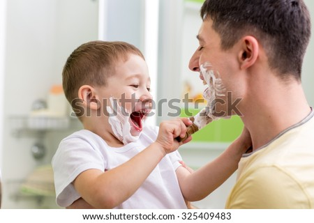 Joyful child little boy applying shaving cream on his father face in bathroom  - stock photo